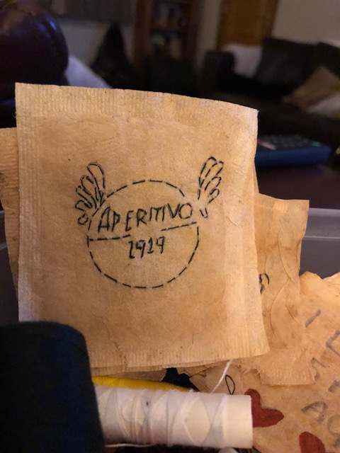 A square paper shape taken from a teabag has the word 'Aperitivo' stitched onto it.
