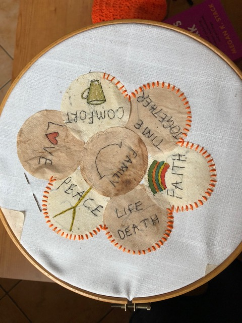 Seven round paper shapes taken from teabags are arranged in a flower design and stitched together. The paper shapes have various words and icons stitched on to them, for example 'love', 'peace' and 'family'.