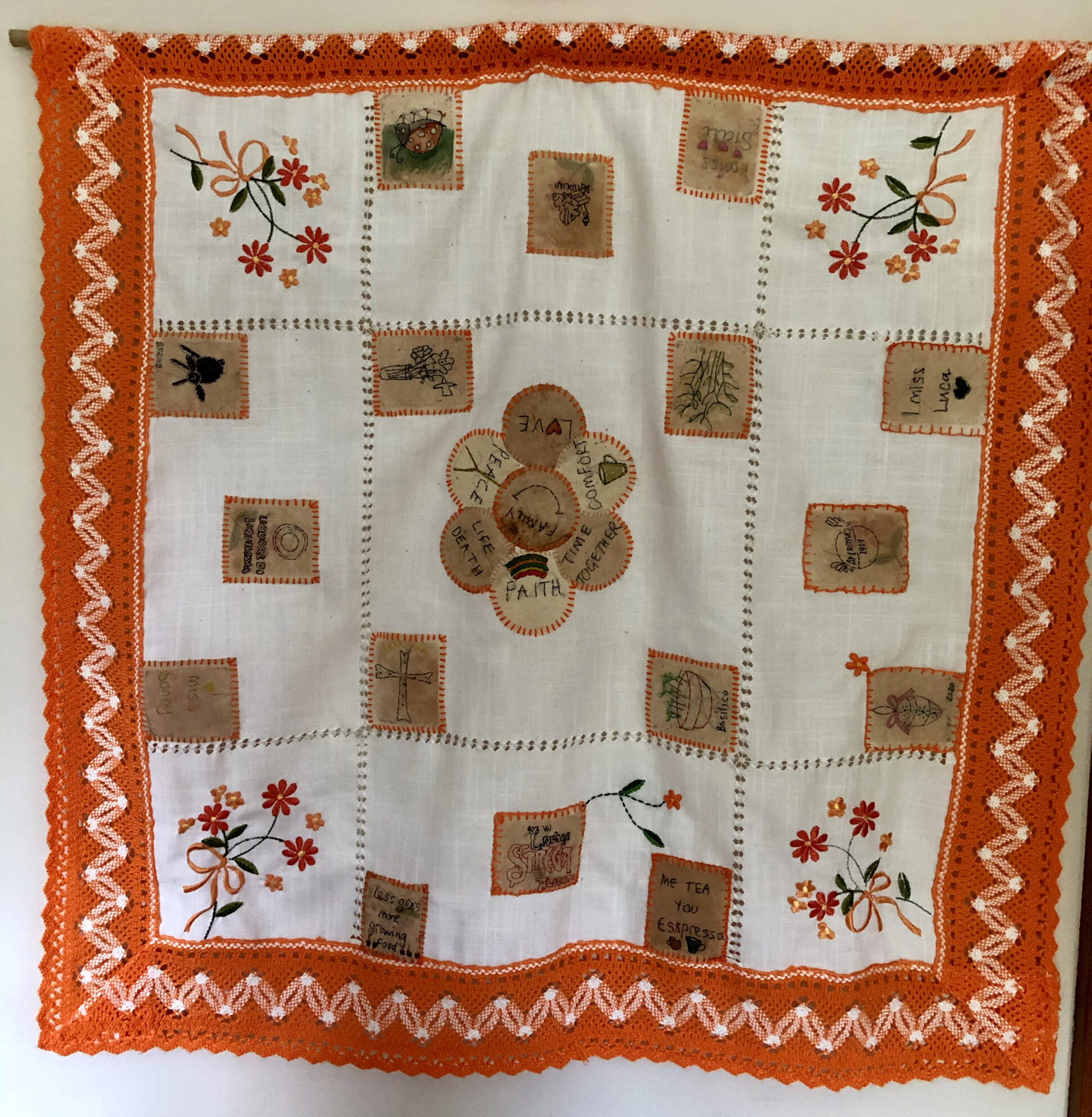 A traditional white Sicilian table cloth with an orange crochet border and floral embroidery. Paper shapes with various words and designs stitched onto them have been added to the tablecloth.