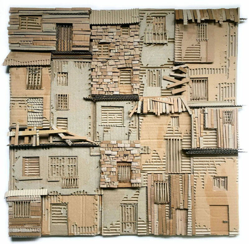 Relief of huts and dwellings that are packed closed together, constructed from corrugated cardboard.