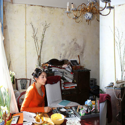 Woman in an orange top and curlers in her hair sitting in a room in an old house with lots of belongings stacked up around her.