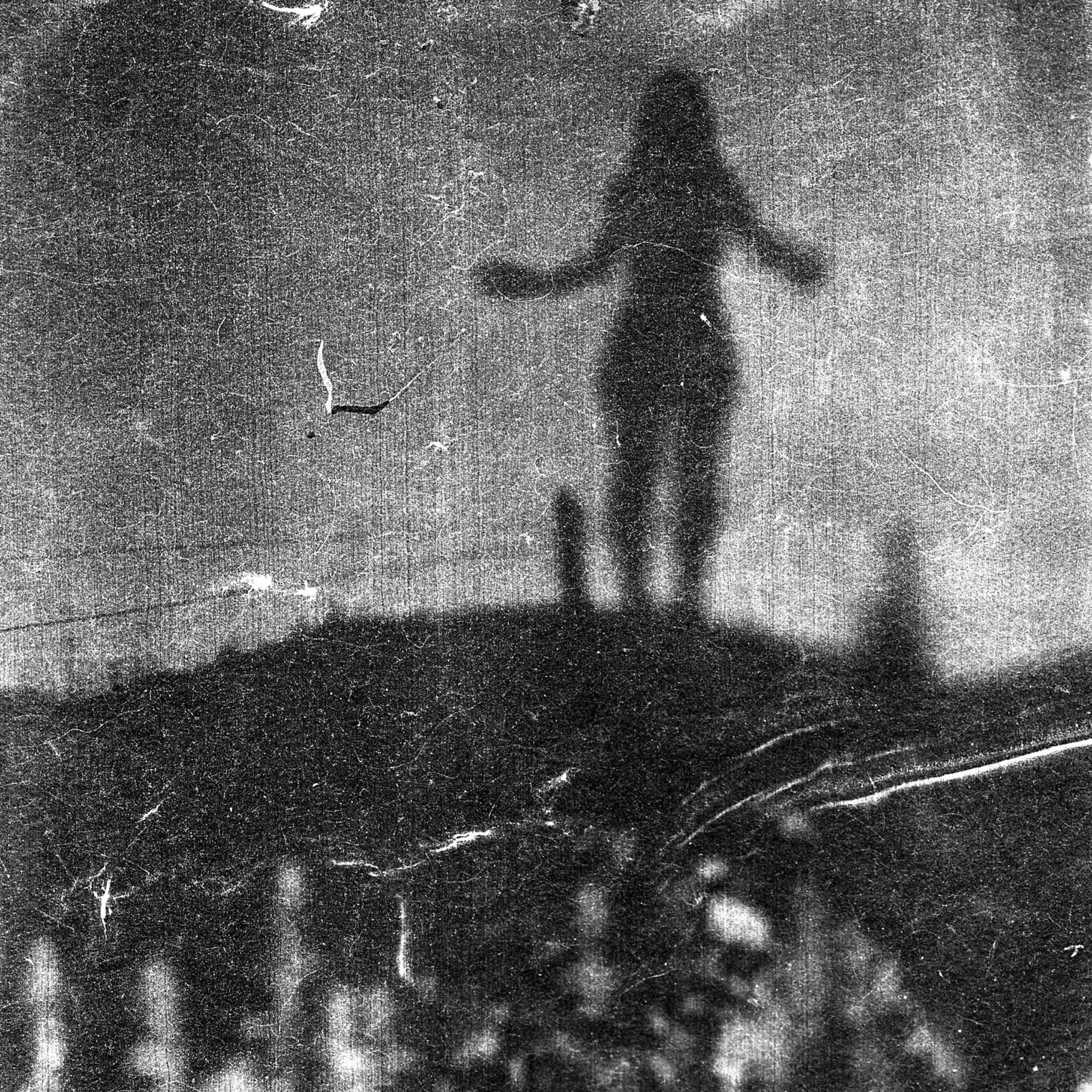 A grainy and hazy black and white photography showing the outline of a woman standing on a mound, the foreground is covered in grass and bushes. o