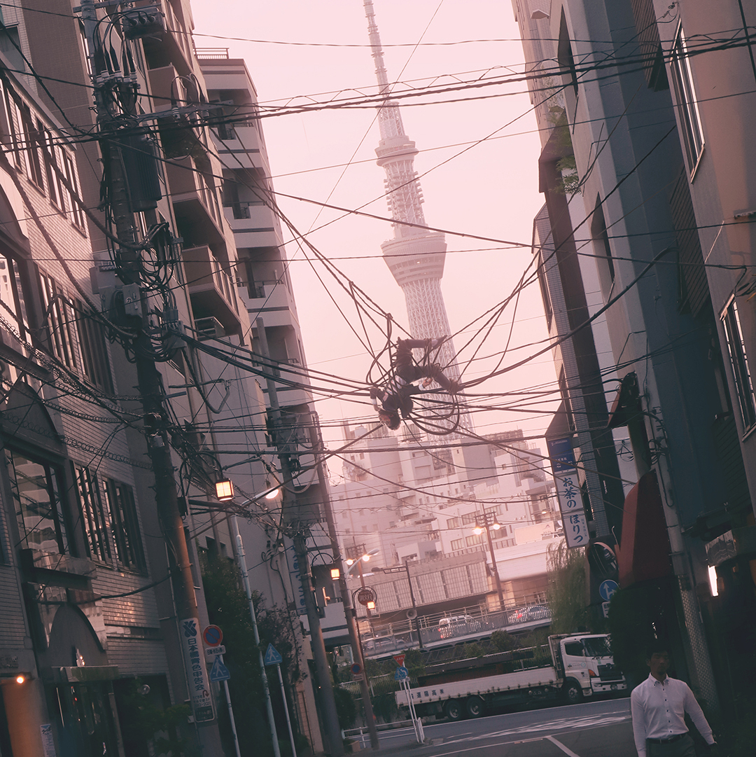 A photography of a street scene in Tokyo, where a man in a suit is suspended among cables hanging in the air, like he is caught in a spider's web.