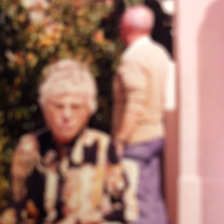 Old and very blurred colour photograph of a couple in a garden. A white haired woman faces the camera and wears a bold patterned shirt, a man with purple trousers faces away from the camera in the background.