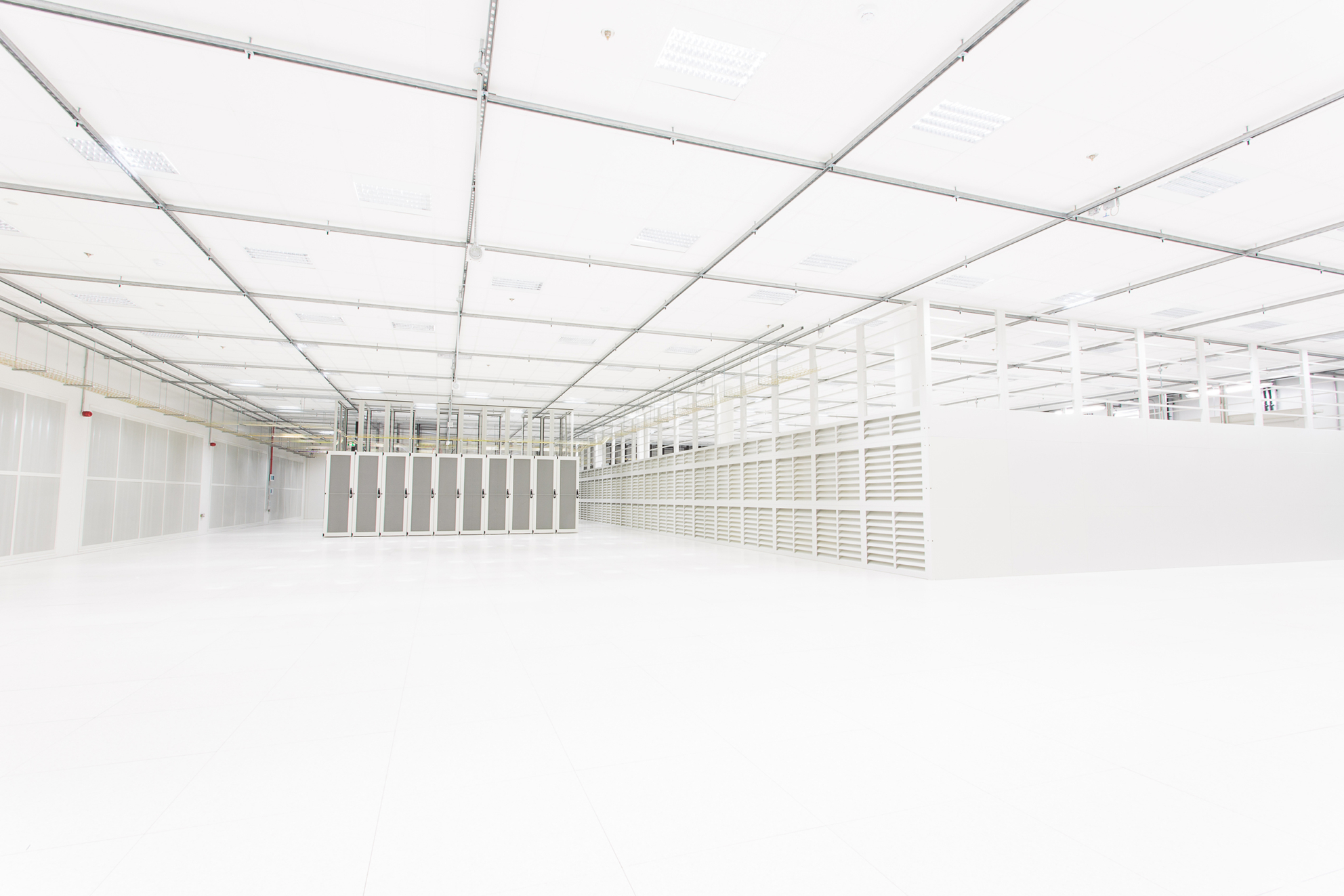 Photograph showing the inside of a computing warehouse, in white and faint tones.