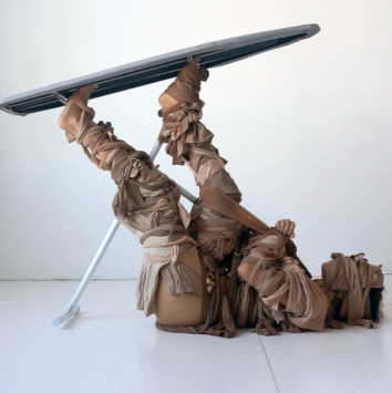 A series of stills from a performance where the artist gradually becomes tied up with an ironing board.