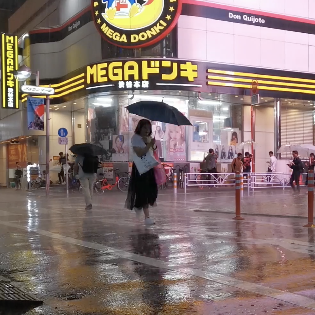 A woman walks down a rainy city streets at dusk, with bright neon lights.