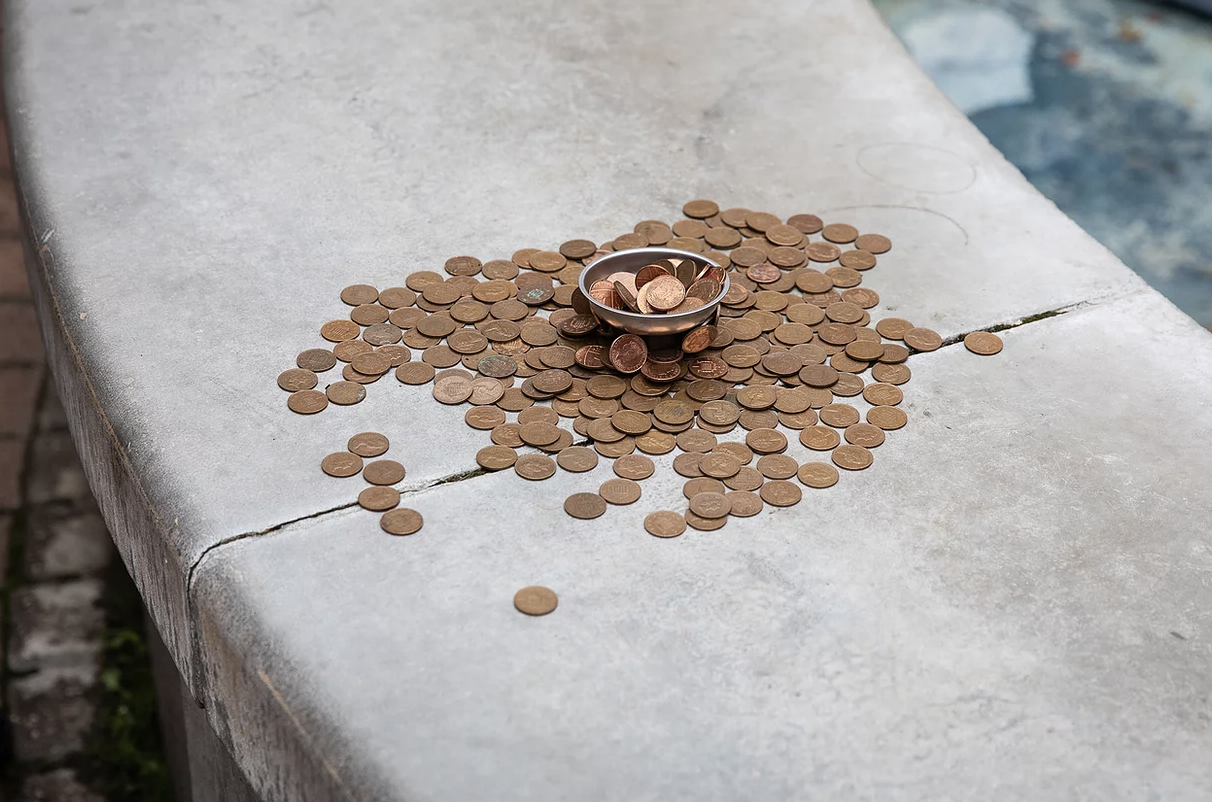 A heap of 1p coins placed on the wide rim of a disused fountain.