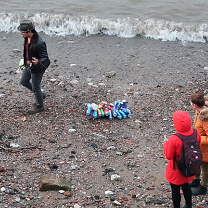 A man walks on a beach pulling a bunch of empty PET drinks cans behind him on a string, whilst people are watching him.